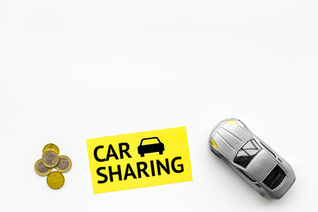 Car sharing concept. Toy car near text car sharing on white background top view copy space