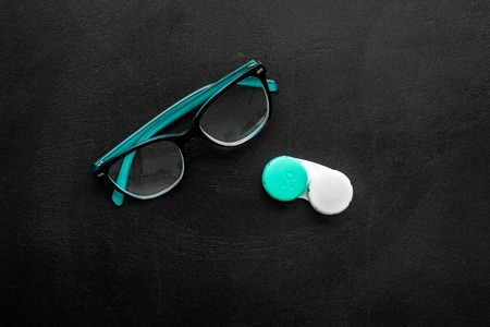 Eyes care. Glasses with transparent lenses and contact lenses on black background top view space for text