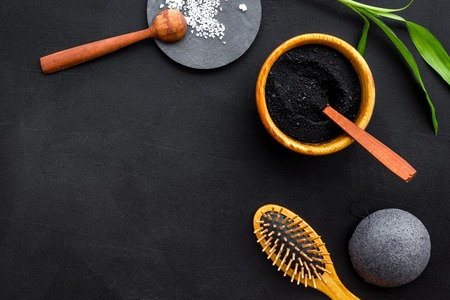 Hair care, hair spa. Cosmetics based on bamboo charcoal powder near comb on black background top view copy space Stock Photo - 117168755