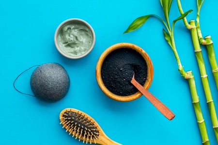 Hair care, hair spa. Cosmetics based on bamboo charcoal powder near comb on blue background top view