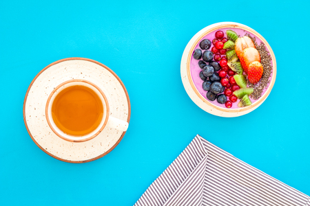 Light breakfast or healthy snack. Acai smoothie bowl with fresh fruits, berries, chia seeds on blue background top view Stock Photo