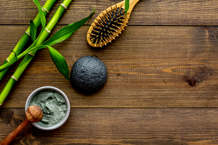 Skin cleansing and detox. Bamboo charcoal powder cosmetics on dark wooden background top view copy space