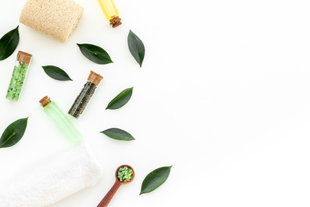 Tea tree spa composition. Fresh tea tree leaves, natural cosmetics, towel on white background top view space for text border