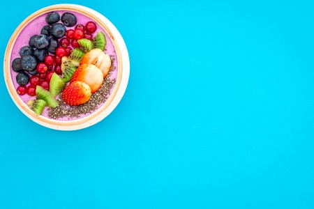 Superfoods. Acai smoothie bowl with fresh fruits, berries, chia seeds on blue background top view copy space