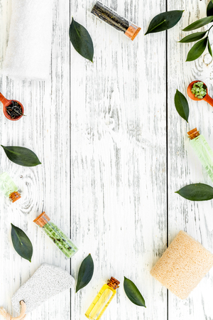 Tea tree spa composition. Fresh tea tree leaves, natural cosmetics, towel on white wooden background top view space for text frame Stock Photo