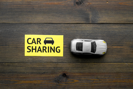 Car sharing concept. Toy car near text car sharing on dark wooden background top view space for text Stock Photo