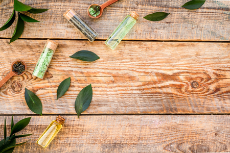 Tea tree oil in small glass bottle near fresh tea tree leaves on rustic wooden background top view space for text border Imagens