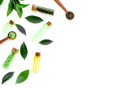 Tea tree oil in small glass bottle near fresh tea tree leaves on white background top view copy space border