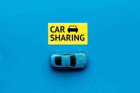 Concept de partage de voiture. Voiture jouet près de l'autopartage de texte sur l'espace de copie de la vue de dessus de fond bleu Banque d'images