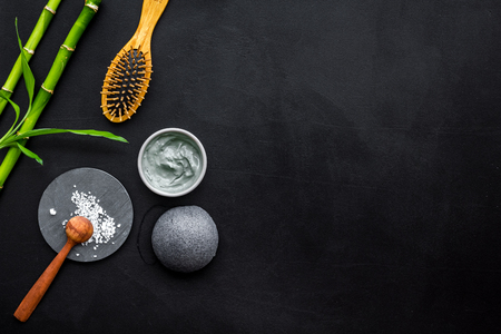 Hair care, hair spa. Cosmetics based on bamboo charcoal powder near comb on black background top view space for text