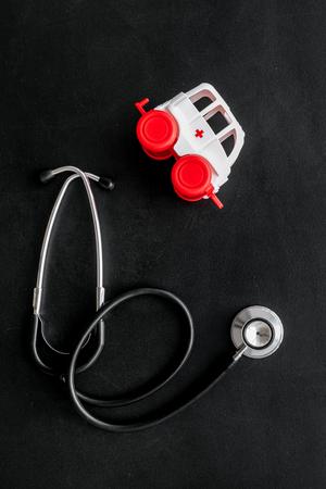 Ambulance service concept. Ambulance vehicle toy near stethoscope on black background top view Stock Photo