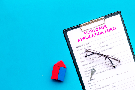 Mortgage concept. Mortgage application form near key and house made of constructor on blue background top view space for text Banco de Imagens
