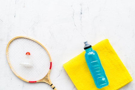 Badminton training concept. Badminton racket, shuttlecock, sport drink and towel on white stone background top view space for text
