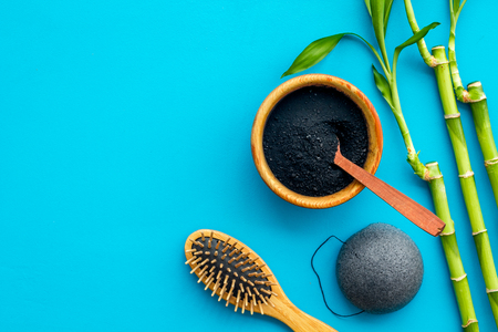 Hair care, hair spa. Cosmetics based on bamboo charcoal powder near comb on blue background top view space for text