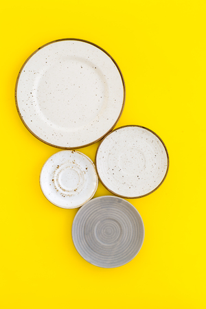 Mockup with plates. Empty ceramic plates on yellow background top view.