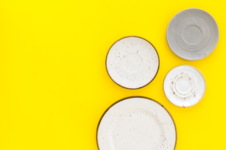 Ceramic plates pattern on yellow background top view. Stock Photo