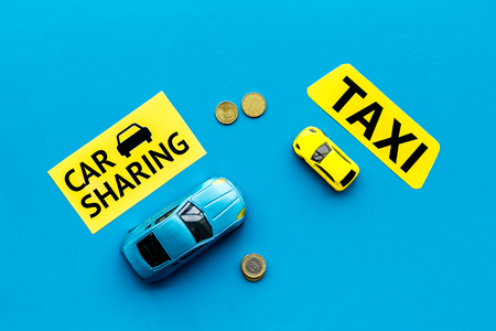 Car sharing vs taxi concept. Comparing car sharing system and taxi. Ship trip concept. Toy cars ans coins on blue background top view.