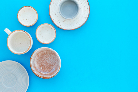 Kitchen concept. Crockery kit. Empty ceramic plates and mugs on blue background top view. Stock Photo