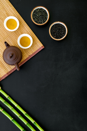 Chinese tea ceremony concept. Tea pot, tea cup, dry tea leaves, bamboo mat on black background top view. Stok Fotoğraf