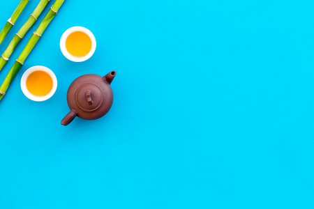 Asian tea traditions. Drink tea. Tea pot near cups of green tea and bamboo decoration on blue background top view.
