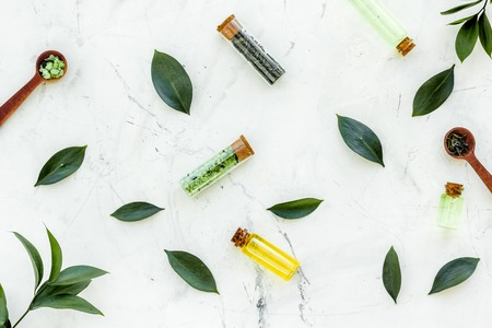 Tea tree oil in small glass bottle near fresh tea tree leaves on white stone background top view.