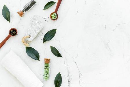 Composizione della stazione termale dell'albero del tè. Foglie fresche dell'albero del tè, cosmetici naturali, asciugamano su sfondo di pietra bianca vista dall'alto. Archivio Fotografico