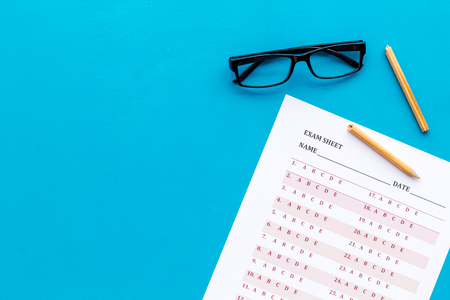 On the exam. Exam sheet, answer near glasses and pencil on blue background top view.