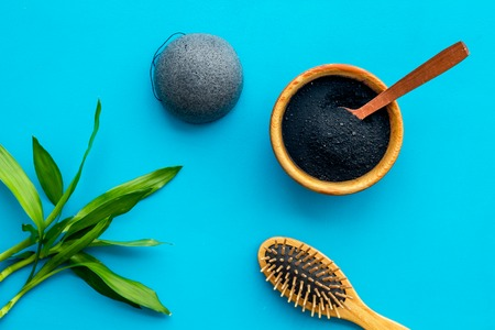 Hair care, hair spa. Cosmetics based on bamboo charcoal powder near comb on blue background top view. Stock Photo - 117280258