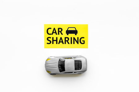 Carsharing concept. Toy car near text car sharing on white background top view.
