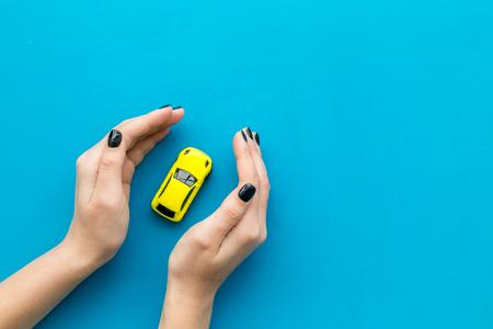 Concepto de seguro de automóvil. Seguridad del auto. Coche de juguete en manos femeninas en la vista superior de fondo azul.