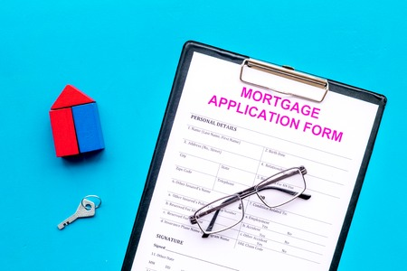 Mortgage concept. Mortgage application form near key and house made of constructor on blue background top view.