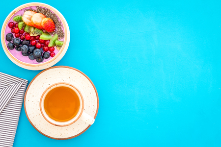 Light breakfast or healthy snack. Acai smoothie bowl with fresh fruits, berries, chia seeds on blue background top view space for text Standard-Bild - 117289769