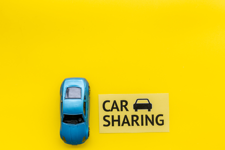 Car sharing concept. Toy car near text car sharing on yellow background top view copy space