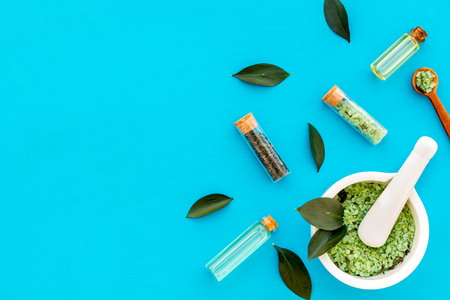 Make cosmetics with tea tree essential oil. Homemade cosmetics. Fresh tea tree leaves, mortar, cosmetics on blue background top view border copy space
