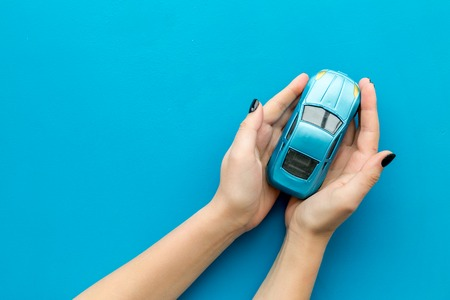 Car insurance concept. Safety of auto. Car toy in female hands on blue background top view copy space