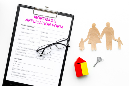 Mortgage concept. Mortgage application form near key and house made of constructor, family cutout on white background top view