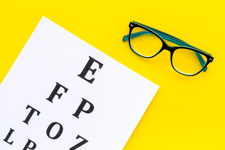 Eye examination. Eyesight test chart and glasses on yellow background top view.