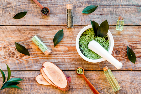 Make cosmetics with tea tree essential oil. Homemade cosmetics. Fresh tea tree leaves, mortar and pestel, cosmetics on rustic wooden background top view. Stock Photo