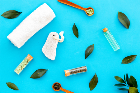 Spa composition with essential tea tree oil. Fresh tea tree leaves, natural cosmetics, towel on blue background top view.