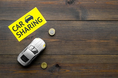 Carsharing concept, carsharing sign. Economical, chip trip. Toy car near coins on dark wooden background top view.