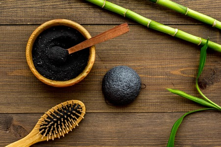 Skin cleansing and detox. Bamboo charcoal powder cosmetics on dark wooden background top view. Stockfoto