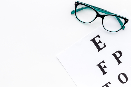 Eye examination. Eyesight test chart and glasses on white background top view.