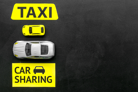 Car sharing vs taxi concept. Comparing car sharing system and taxi. Toy cars and text signs on black background top view.
