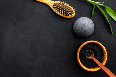 Hair care, hair spa. Cosmetics based on bamboo charcoal powder near comb on black background top view copy space