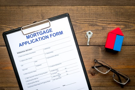 Mortgage concept. Mortgage application form near key and house made of constructor on dark wooden background top view
