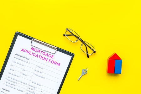 Mortgage concept. Mortgage application form near key and house made of constructor on yellow background top view copy space