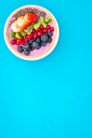 Superfoods. Acai smoothie bowl with fresh fruits, berries, chia seeds on blue background top view.