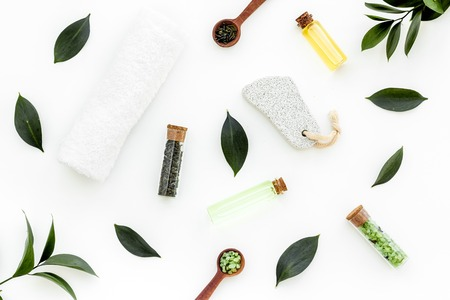 Spa composition with essential tea tree oil. Fresh tea tree leaves, natural cosmetics, towel on white background top view.