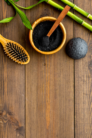 Skin cleansing and detox. Bamboo charcoal powder cosmetics on dark wooden background top view. Stock Photo