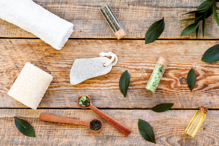 Spa composition with essential tea tree oil. Fresh tea tree leaves, natural cosmetics, towel on wooden background top view. Stock Photo
